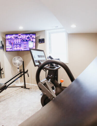 corner of home gym with tv on wall and black exercise equipment facing wall mirror