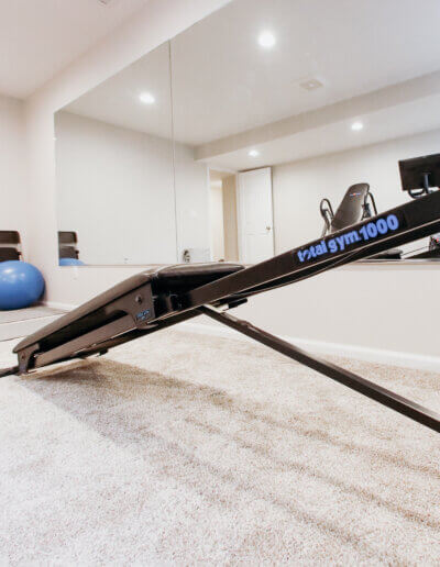 close up picture of black rowing machine near exercise ball and dumbells on new gray carpeting