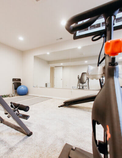 close up picture of black exercise bike with gym equipment and wall mirror in the background and TV in the corner