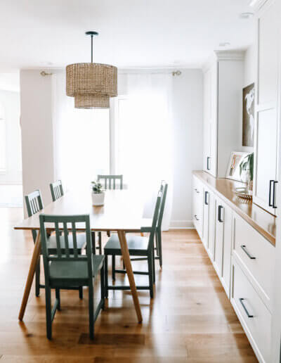 dining room table set on left with rattan pendant light above and white shelving units along wall to the right