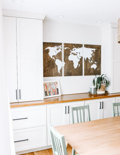 top down view of wooden kitchen table with the tops of green chairs, built-in white shelving units along the back wall with the wooden map wall hanging between them and above small wood countertop. Rattan pendant hanging above dining table