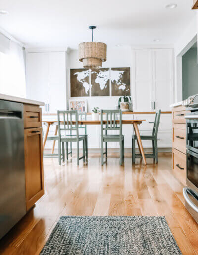 looking between the kitchen island and kitchen countertops against the wall, a black and gray woven runner rug between them with dining room in the background