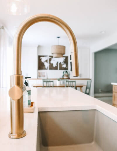 Close up image of gold faucet with blurry photo of dining room in the background of a wood rattan pendant light and a wood map wall hanging