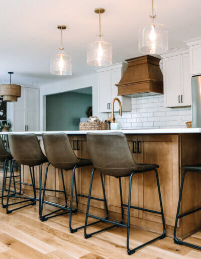 five leather barstools tucked under wood kitchen island with white counter top and glass/gold pendant lights above. Dining area seen in the background with a white tile backsplash and kitchen counter against wall with white shelves