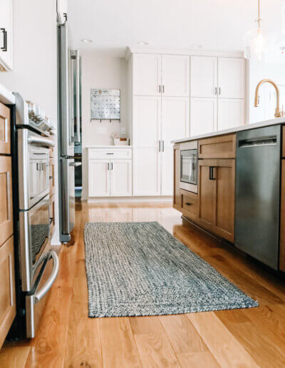 shot down along finished wood kitchen cabinets, gray/silver appliances with a dark gray woven rug runner between kitchen island and counters along wall with white shelving in the background