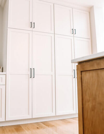 down, up shot of kitchen island corner and wall next to it, showing white cabinet units along opposite kitchen wall with metal calendar above countertop