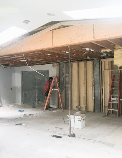 exposed wooden beamed ceiling overhang into room with insulation coming down onto concrete floor