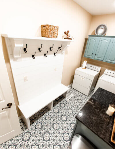 downward shot of laundry room with black countertop on right side, washer/dryer in back with teal cabinets above and white hooks/compartments on left side