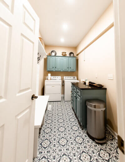 shot down into laundry room with white/blue ornate tiled flooring, soft orange walls, teal cabinetry and white washer/dyer