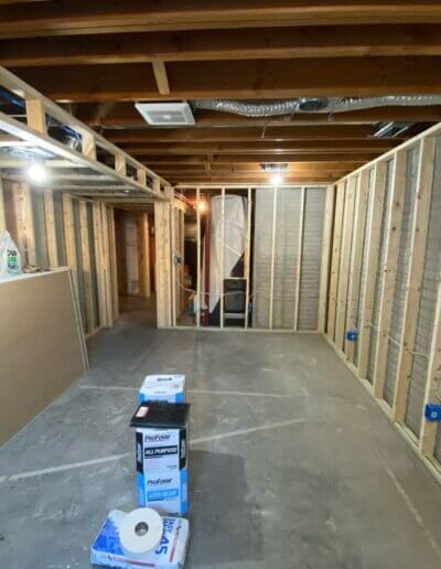 wide shot of new wooden framing for walls and ceiling of basement