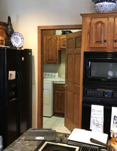 view of dark wood kitchen and black appliances with door on wall open to laundry room